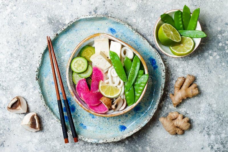 Ciotola di minestra asiatica delle tagliatelle del udon del vegano con lo zenzero ed i funghi brodo, tofu, piselli improvvisi, zu fotografia stock