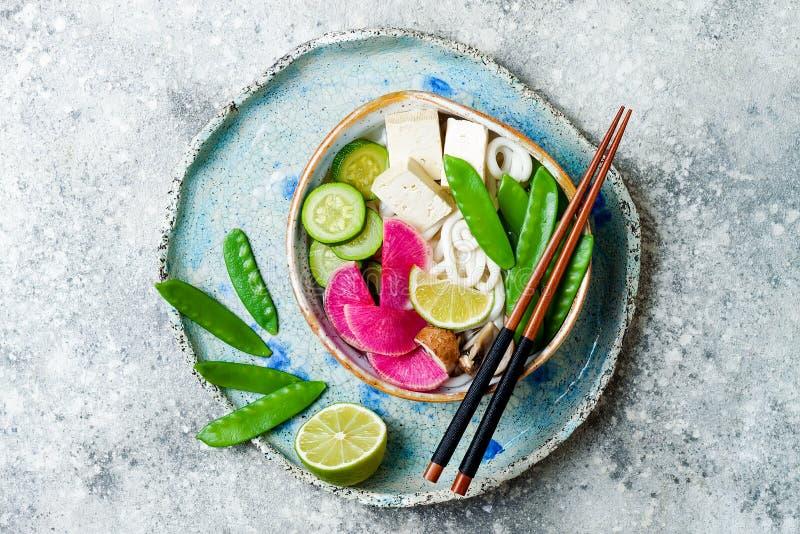 Ciotola di minestra asiatica delle tagliatelle del udon del vegano con lo zenzero ed i funghi brodo, tofu, piselli improvvisi, zu fotografie stock