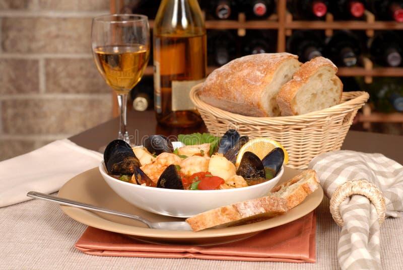 Ciotola di minestra dei frutti di mare con vino e pane rustico immagine stock