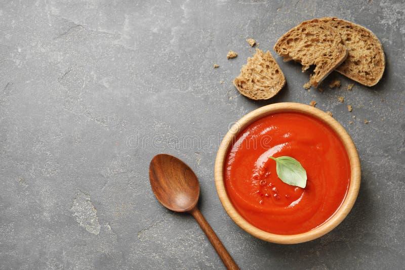Ciotola di minestra e di pane casalinghi freschi del pomodoro su fondo grigio, vista superiore fotografie stock libere da diritti