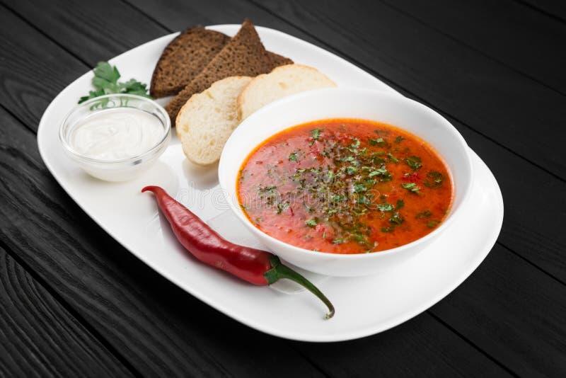Ciotola di minestra rossa con le verdure ed il peperoncino su un fondo di legno posteriore fotografie stock