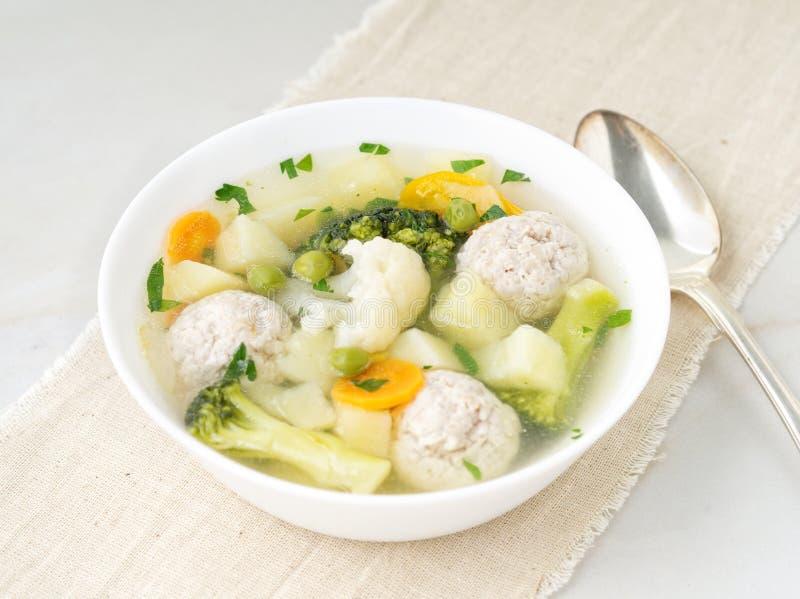 Ciotola di minestra, di tazza di brodo e delle verdure, di polpette fatte del tacchino e di pollo, vista superiore fotografie stock