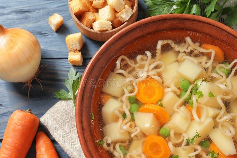 Ciotola di minestra di verdura casalinga fresca con gli ingredienti sulla tavola di legno blu, fotografia stock