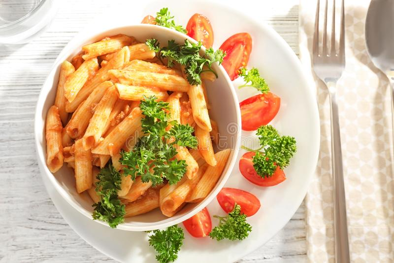 Ciotola di pasta deliziosa con salsa bolognese sulla tavola immagine stock