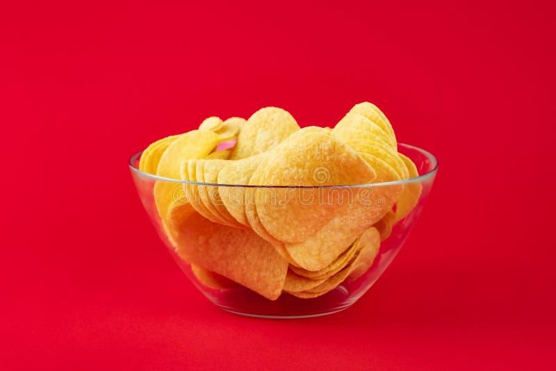 Ciotola di patatine fritte nel fondo rosso luminoso Imag di Minimalistic fotografie stock
