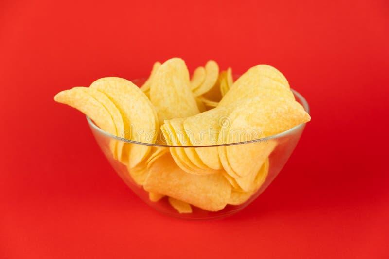 Ciotola di patatine fritte nel fondo rosso luminoso Imag di Minimalistic fotografie stock libere da diritti