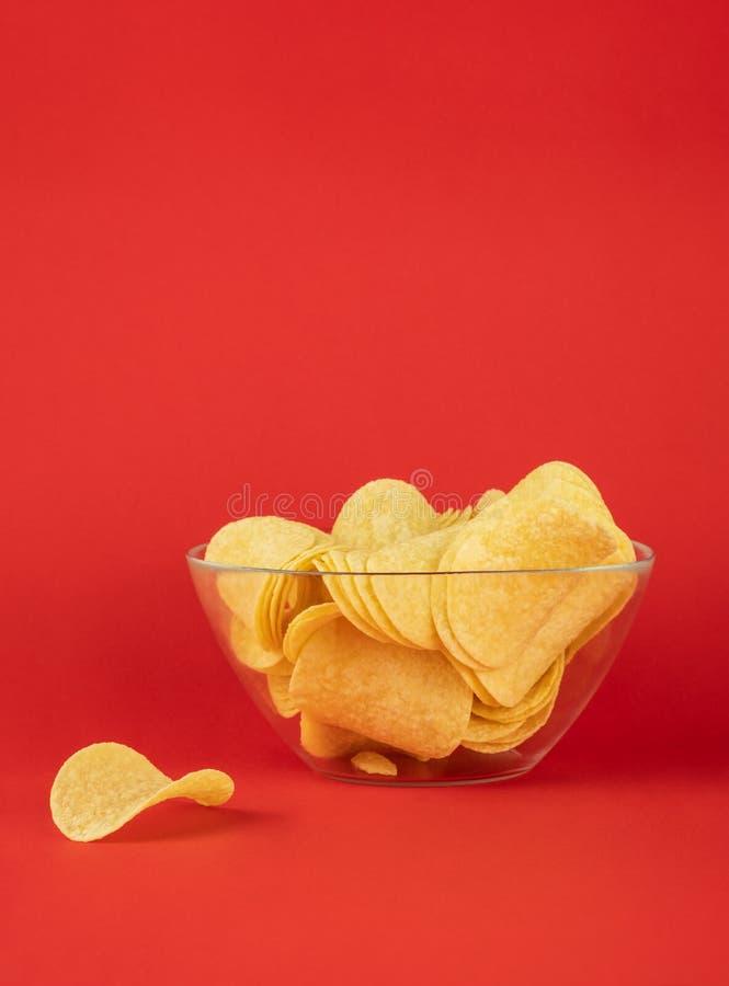 Ciotola di patatine fritte nel fondo rosso luminoso Imag di Minimalistic immagine stock