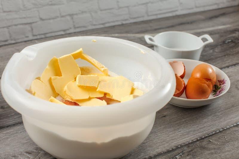 Ciotola di plastica bianca con burro, il tuorlo d'uovo, la farina ed il sale, pronti fotografie stock libere da diritti