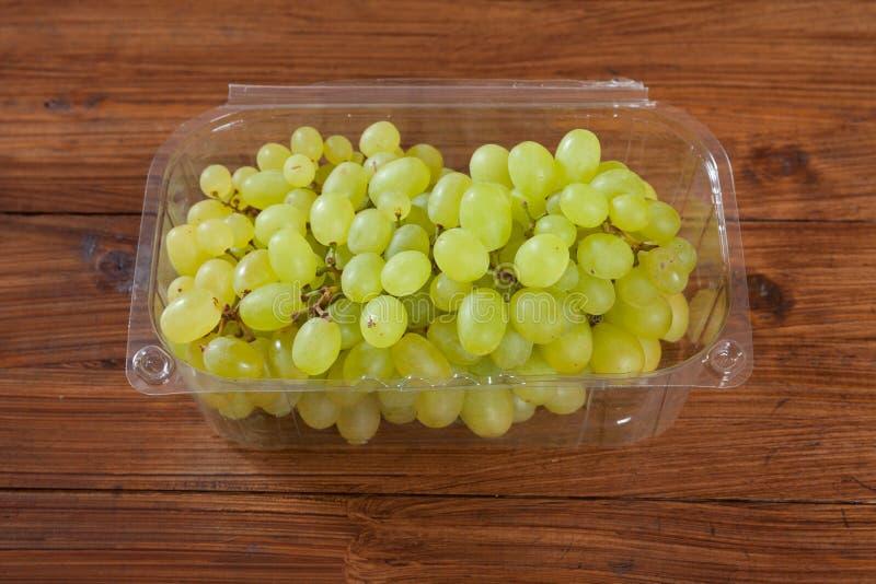 Ciotola di plastica con l'uva verde fotografie stock
