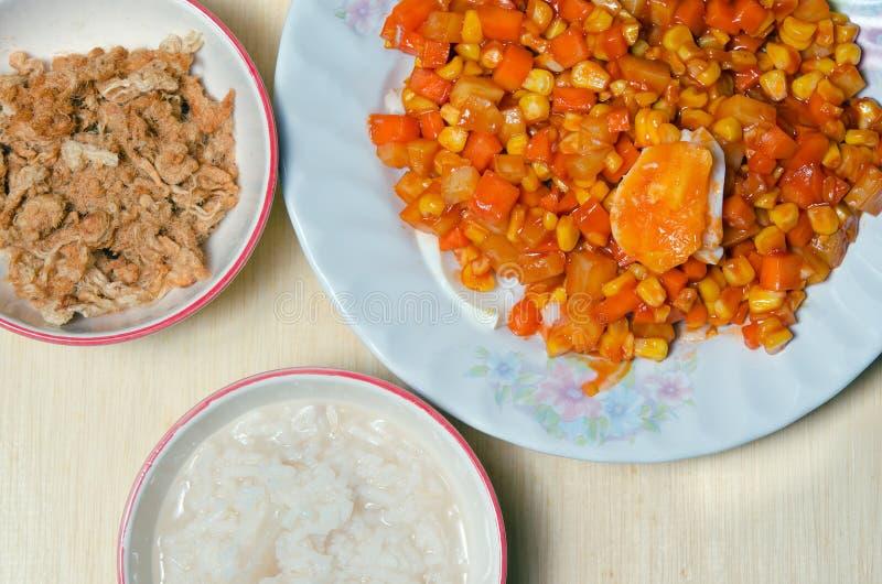 Ciotola di porridge del riso con carne di maiale o filo di seta e salte tagliuzzati della carne di maiale fotografia stock
