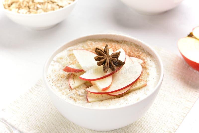 Ciotola di porridge dell'avena con le fette e la cannella rosse della mela immagini stock libere da diritti