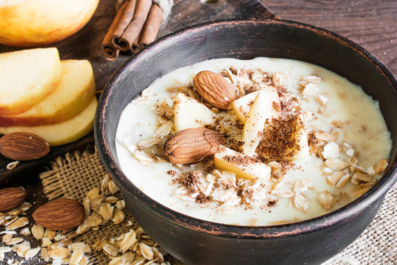 Ciotola di porridge della farina d'avena con la mela, la cannella e le mandorle fotografia stock