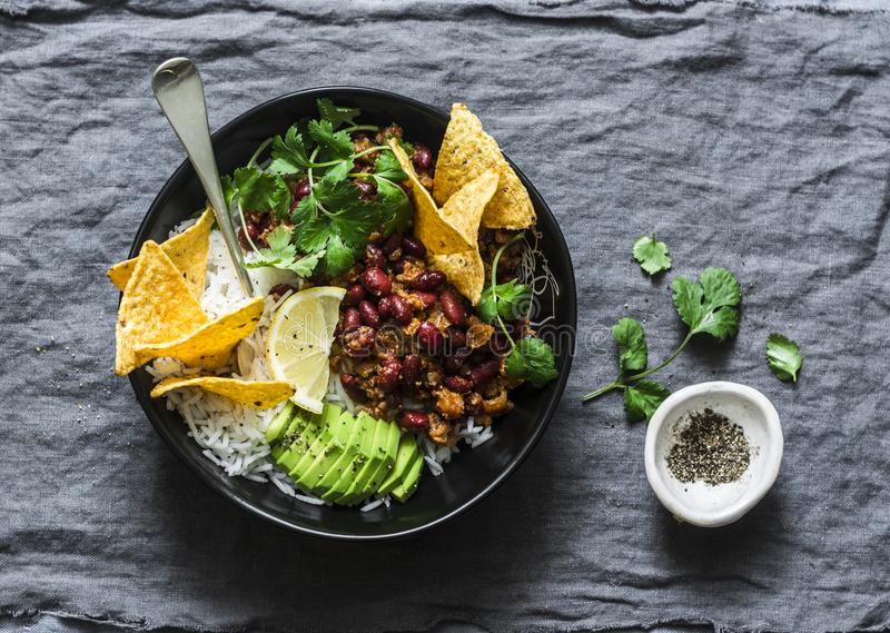 Ciotola di riso del burrito con le patatine fritte di tortiglia, il coriandolo e l'avocado su fondo grigio fotografia stock