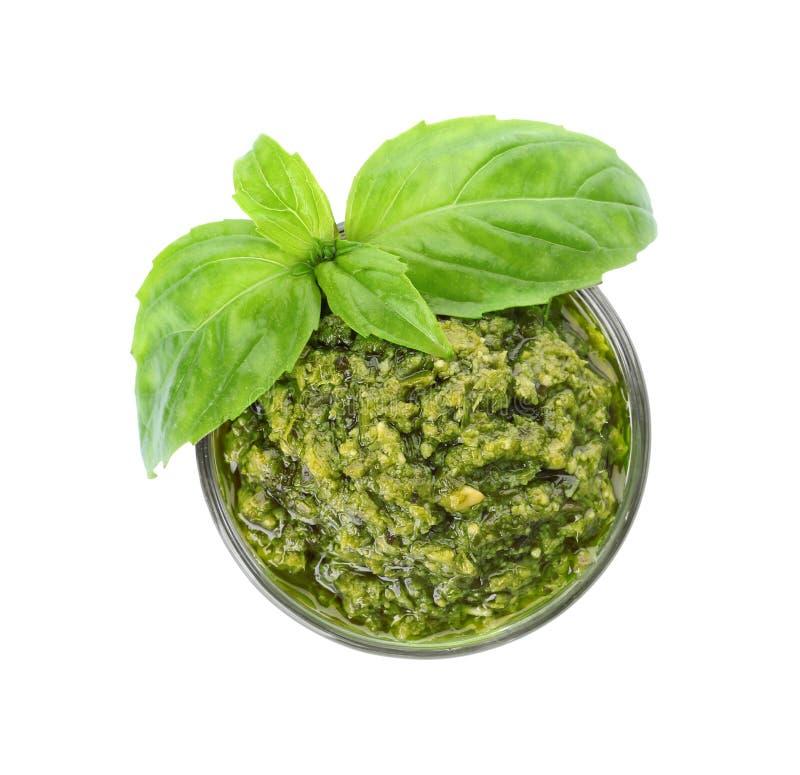Ciotola di salsa saporita di pesto con le foglie del basilico isolate su bianco fotografie stock libere da diritti