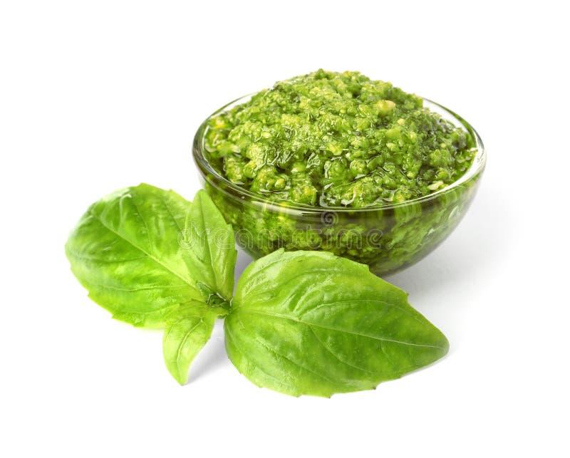 Ciotola di salsa saporita di pesto con le foglie del basilico su bianco fotografia stock libera da diritti