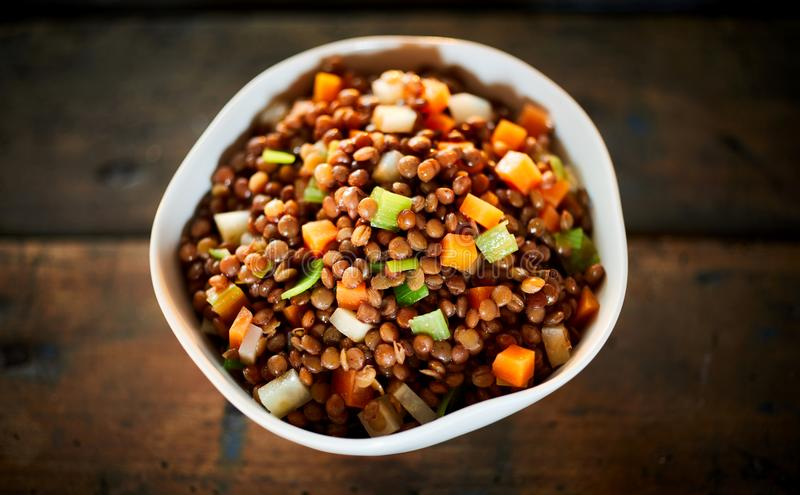 Ciotola di stufato sano della lenticchia rossa con le verdure immagine stock