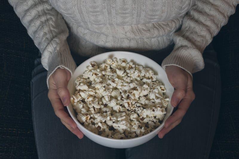 Ciotola di tenuta femminile non identificabile di popcorn sul suo rivestimento fotografia stock