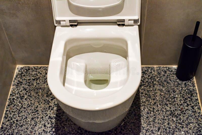 Ciotola di toilette con sciacquone nella fine del lavabo pubblico fotografie stock