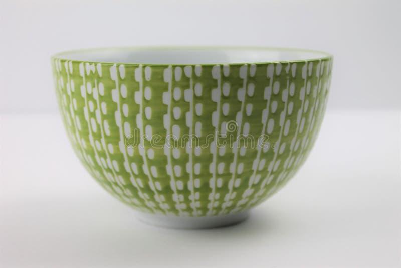 Ciotola di vetro bianca decorativa e di verde su un fondo bianco isolato immagini stock