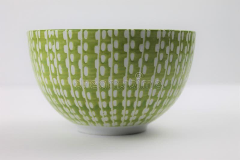 Ciotola di vetro bianca decorativa e di verde su un fondo bianco isolato fotografie stock
