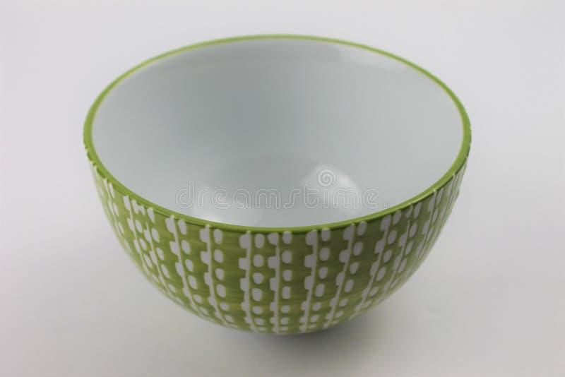 Ciotola di vetro bianca decorativa e di verde su un fondo bianco isolato fotografia stock