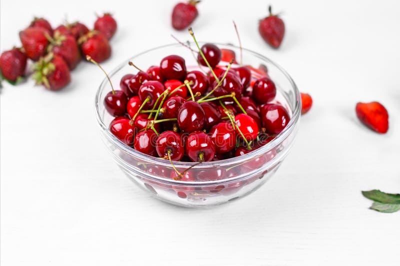Ciotola di vetro con le ciliege rosse mature Cibo sano La frutta è una fonte di vitamine fotografia stock