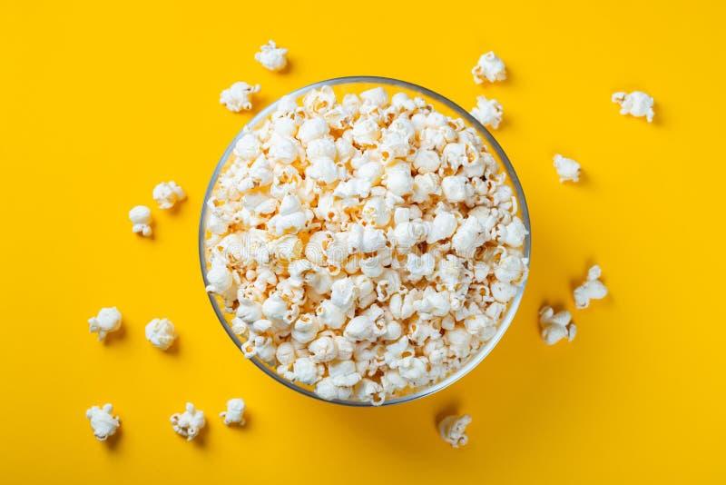 Ciotola di vetro con popcorn salato su fondo giallo Vista superiore con lo spazio della copia Disposizione piana immagine stock libera da diritti