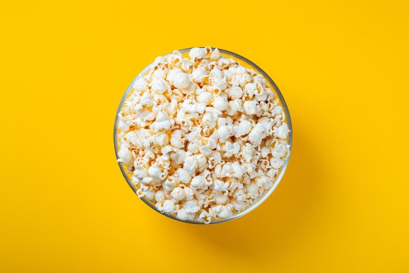 Ciotola di vetro con popcorn salato su fondo giallo Vista superiore con lo spazio della copia Disposizione piana fotografia stock