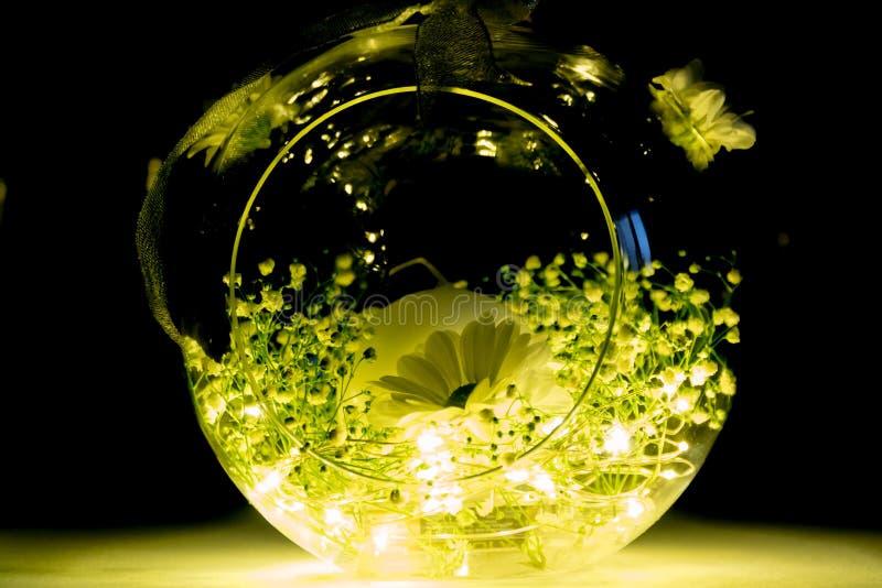 Ciotola di vetro decorativa della candela con i fiori e le luci fotografie stock