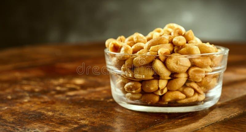 Ciotola di vetro di arachidi salate arrostite fresche immagine stock