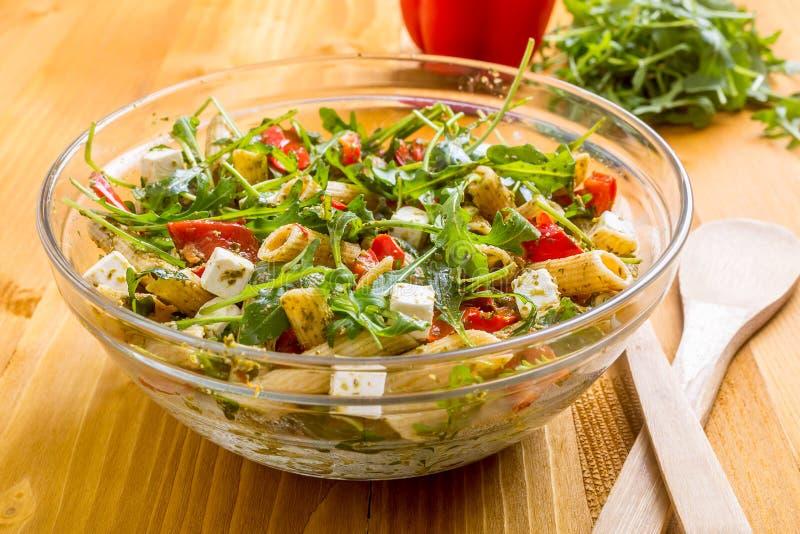 Ciotola di vetro di insalata sana della pasta, di Rucola, di pesto e della feta fotografia stock libera da diritti