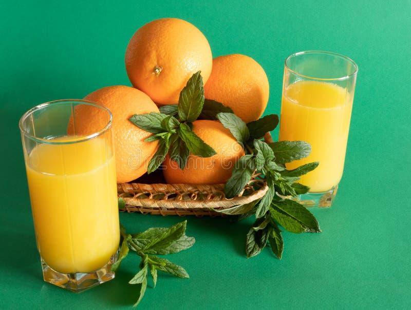 Ciotola di vimini con le arance decorate con la menta, accanto ad un vetro con succo d'arancia su un fondo verde fotografia stock libera da diritti