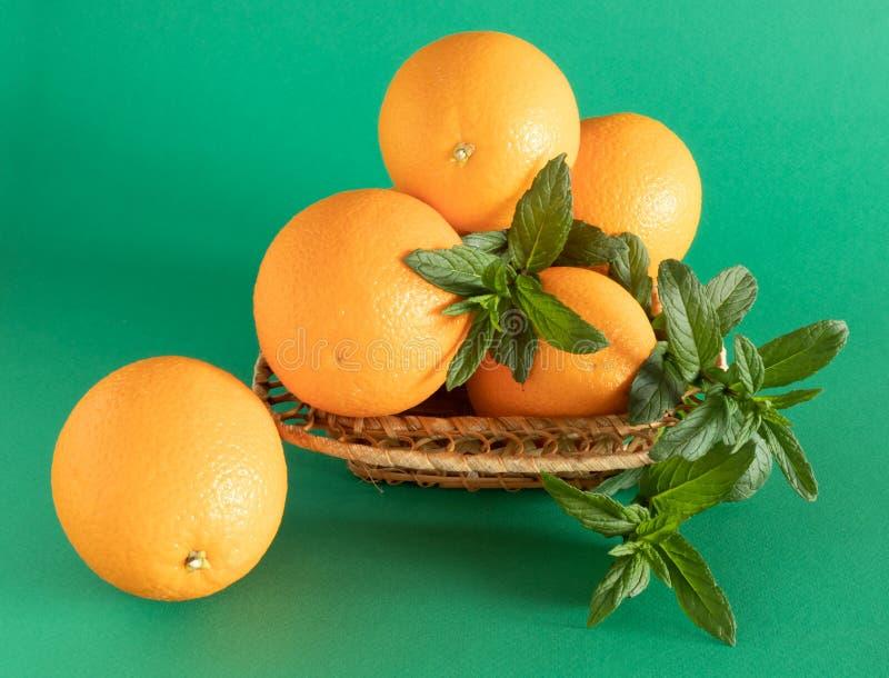 Ciotola di vimini con le arance e la menta su fondo verde immagini stock libere da diritti