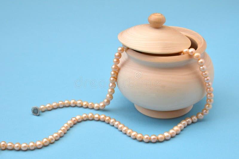 Ciotola di zucchero di legno leggera con un coperchio e una serie di perle di rosa di mare su un fondo blu immagini stock libere da diritti