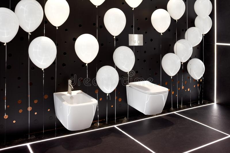 Ciotola e bidet di toilette bianchi moderni del pendente nell'interno del bagno nero con le palle gonfiabili bianche fotografie stock libere da diritti