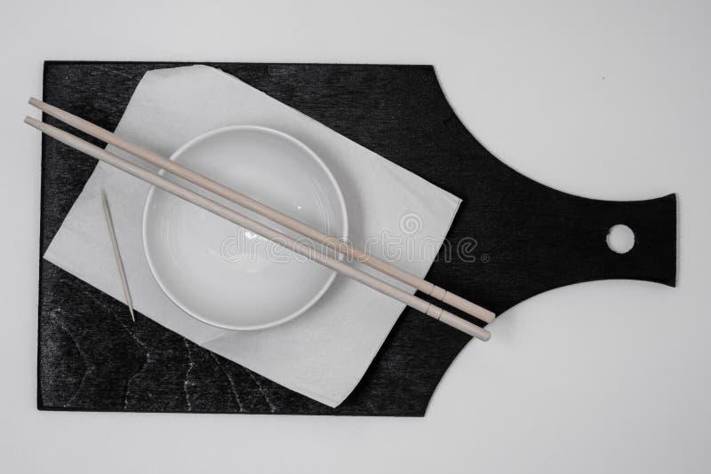 Ciotola e tovagliolo bianchi, stuzzicadenti, bastoncini sul bordo nero fotografia stock