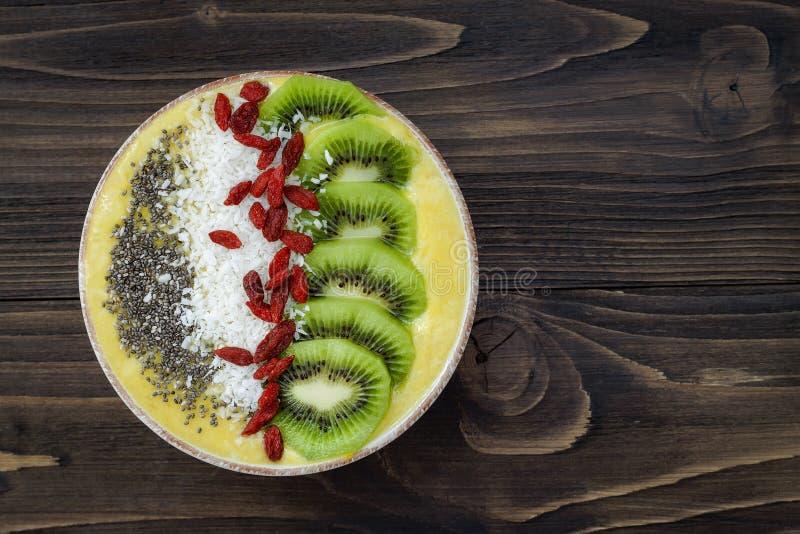 Ciotola gialla del frullato del superfood dell'agrume con il kiwi, semi di chia, noce di cocco, guarnizioni della bacca di goji V fotografia stock libera da diritti