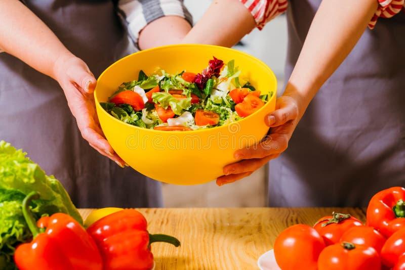 Ciotola gialla dell'insalata di verdure di stile di vita del vegano della famiglia immagine stock libera da diritti