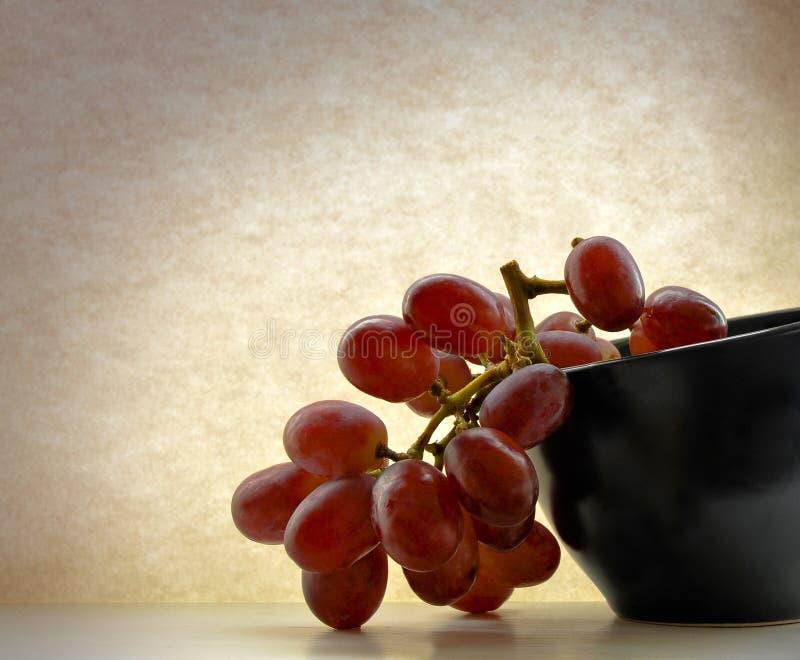 Ciotola nera dell'uva rossa fotografia stock libera da diritti