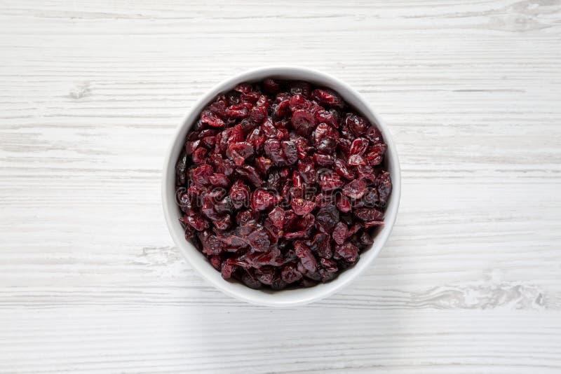 Ciotola piena di mirtilli rossi organici asciutti sopra superficie di legno bianca, vista superiore Sopraelevato, da sopra, dispo fotografia stock libera da diritti