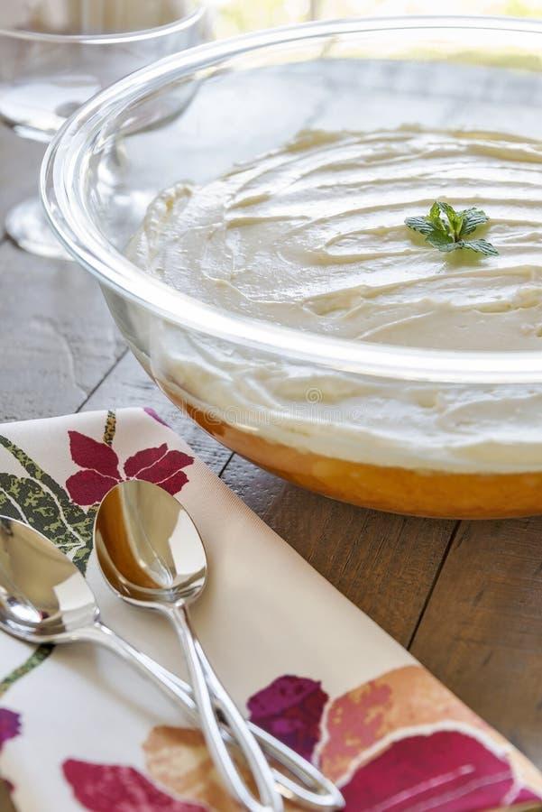 Ciotola in pieno di dessert Gelificare-o con una guarnizione montata cremosa immagine stock