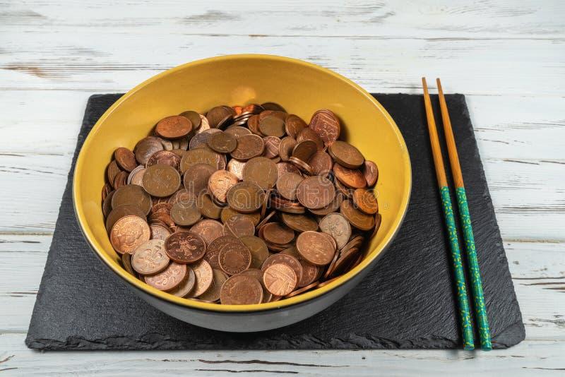 Ciotola in pieno di monete di sterlina e dei bastoncini Concetto immagini stock libere da diritti