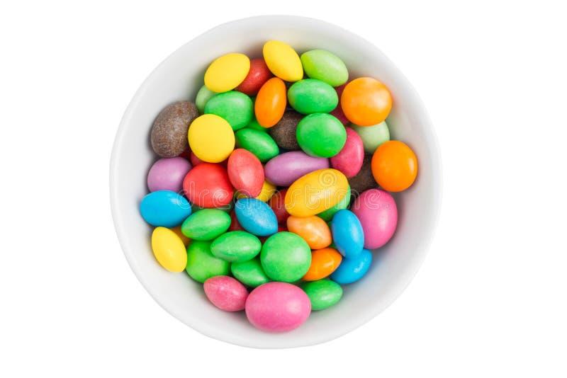 Ciotola riempita di caramella multicolore deliziosa isolata su fondo bianco immagine stock