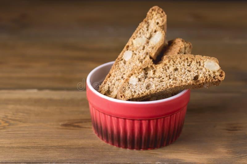 Ciotola rossa con lo spazio di legno della copia del fondo di Biscotti Cantucci della mandorla dei dolci dei biscotti italiani al immagine stock
