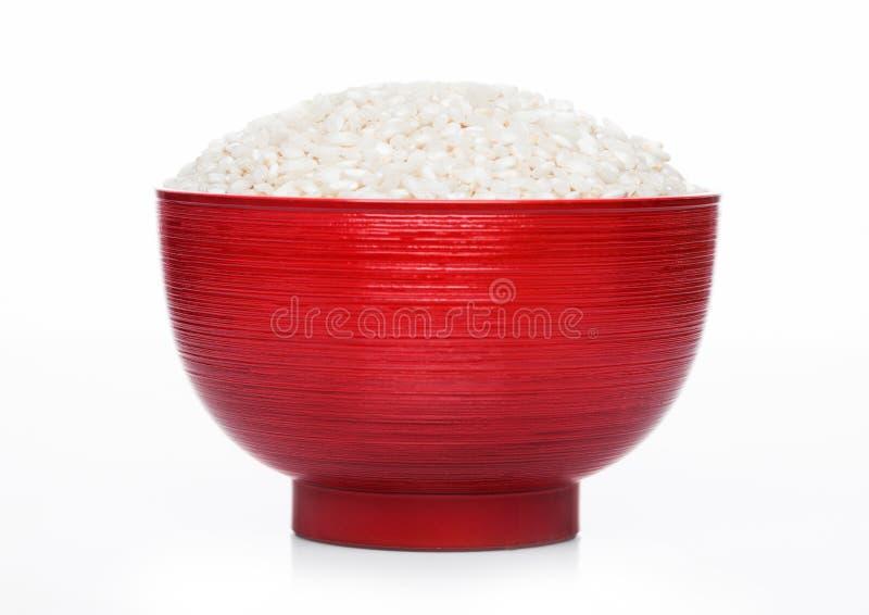 Ciotola rossa di riso organico crudo del risotto di arborio su fondo bianco Alimento sano immagine stock