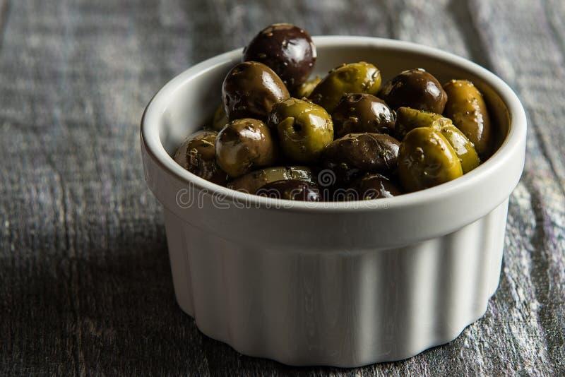 Ciotola rustica di olive su legno immagine stock