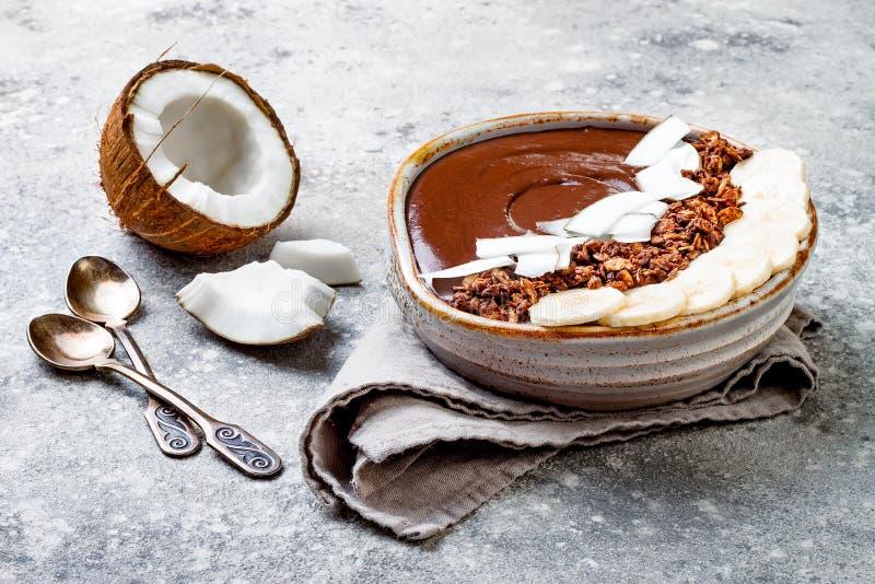Ciotola sana della prima colazione La ciotola del frullato della banana del cioccolato con la noce di cocco si sfalda, granola, f immagini stock libere da diritti