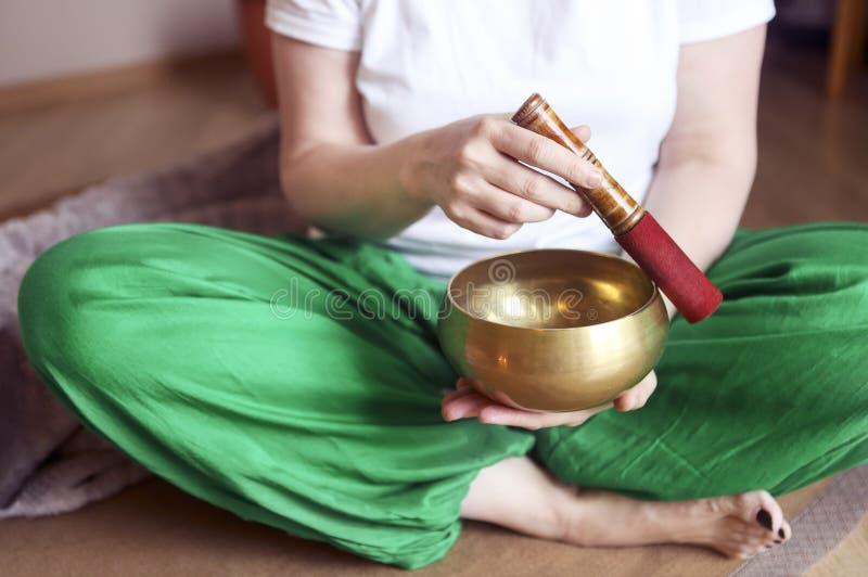 Ciotola tibetana di canto nelle mani di una donna fotografia stock
