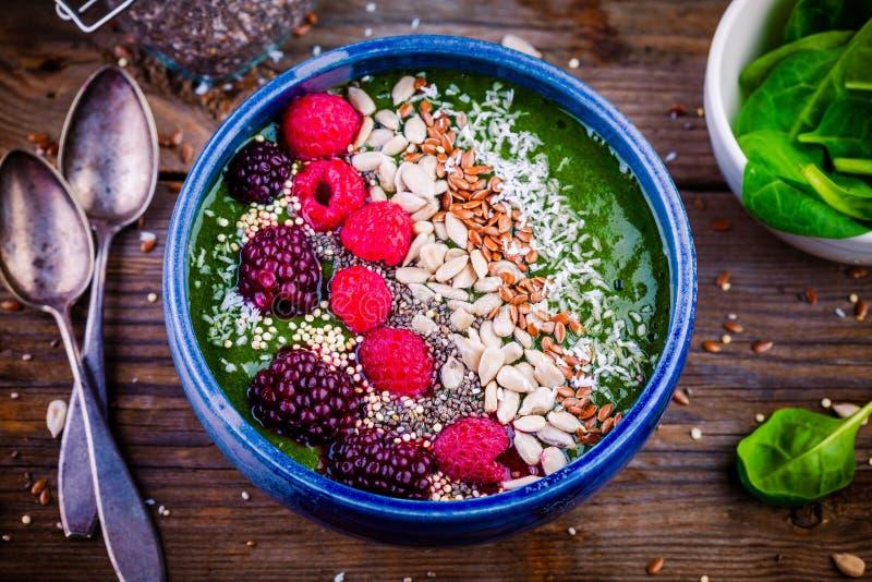 Ciotola verde del frullato degli spinaci con il lampone, la mora, i semi di lino, i semi di girasole ed i chip della noce di cocc fotografie stock libere da diritti