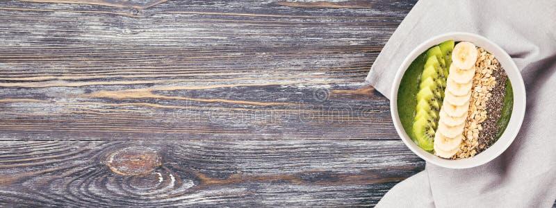 Ciotola verde del frullato sulla tavola di legno rustica fotografia stock